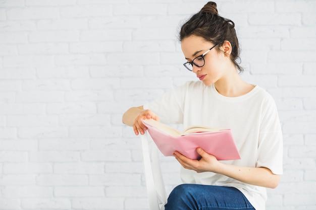 Młoda kobieta czyta na krześle