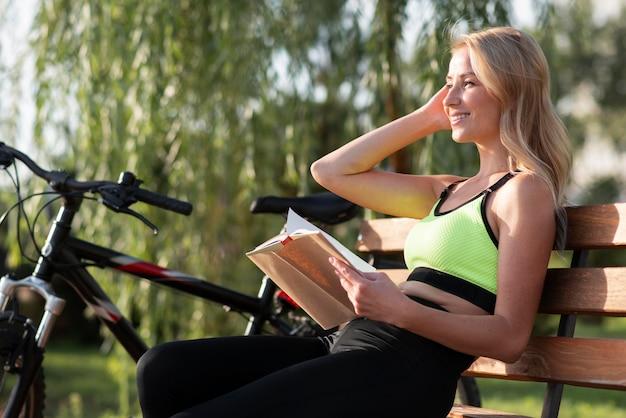 Młoda kobieta czyta na ławce