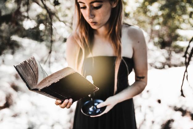 Młoda kobieta czyta starą książkę z świeczką w drewnach