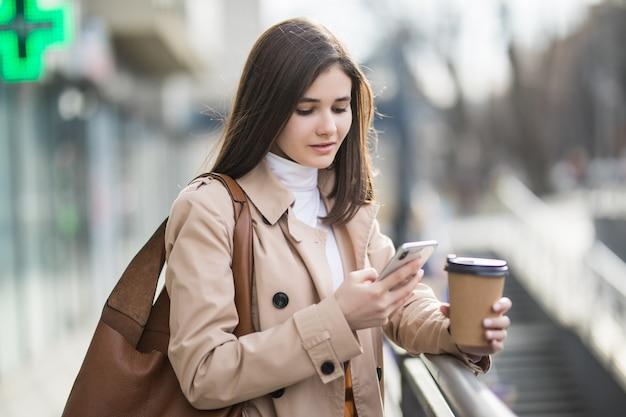 Młoda kobieta czyta wiadomości w swoim telefonie na zewnątrz