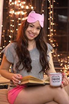 Młoda kobieta, czytając książkę i pijąc herbatę