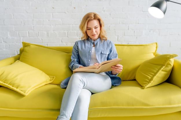 Młoda kobieta, czytając książkę na przytulnej żółtej kanapie