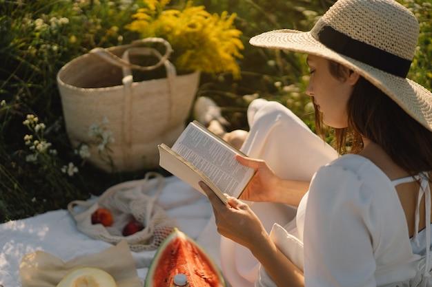 Młoda kobieta czytająca książkę w plenerze czytanie i relaks