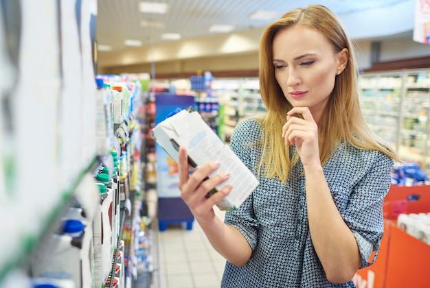 Młoda kobieta czytająca mleko na etykiecie