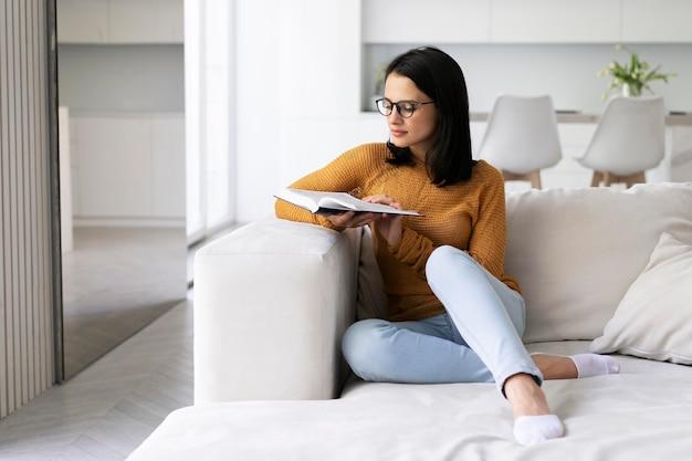 Młoda kobieta czytająca z książki w domu