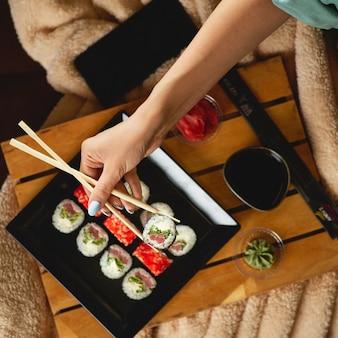Młoda kobieta, czytanie książki i jedzenie sushi na kanapie w domu. widok z góry