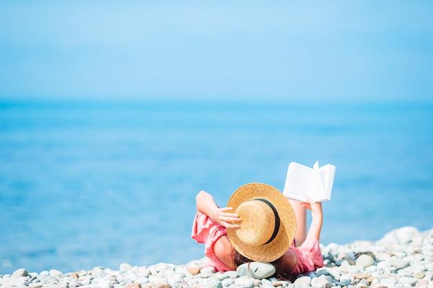 Młoda kobieta, czytanie książki podczas tropikalnej białej plaży