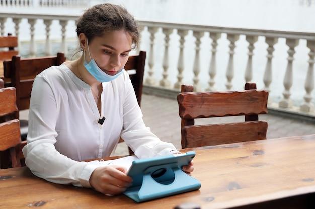 Młoda kobieta, czytanie na tablecie, siedząc przy stole w kawiarni ulicy