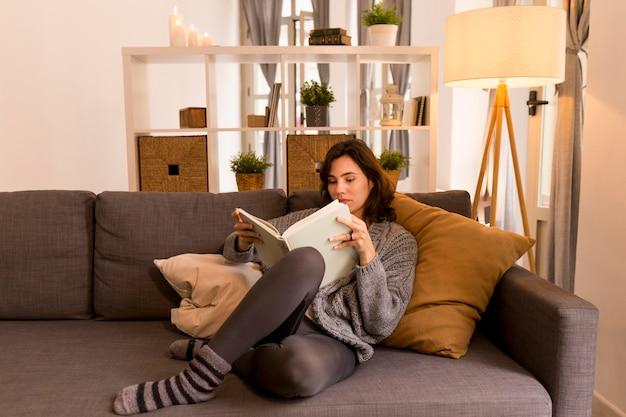 Młoda kobieta, czytanie w salonie