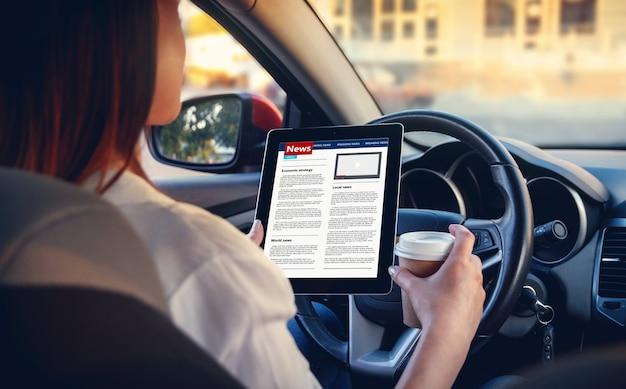 Młoda kobieta, czytanie wiadomości z tabletem w rękach, siedząc w samochodzie