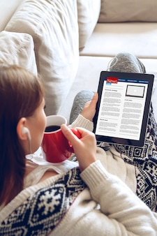 Młoda kobieta, czytanie wiadomości za pomocą tabletu, siedząc na kanapie w domu