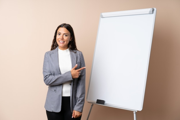Młoda kobieta, dając prezentacji na białej tablicy, wskazując na bok, aby przedstawić produkt