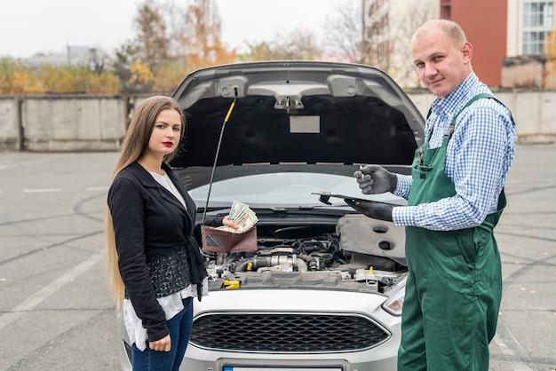 Młoda kobieta daje dolary mechanikowi za usługi