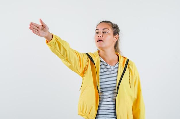 Młoda kobieta daje instrukcje w kurtce, koszulce i wygląda pewnie. przedni widok.