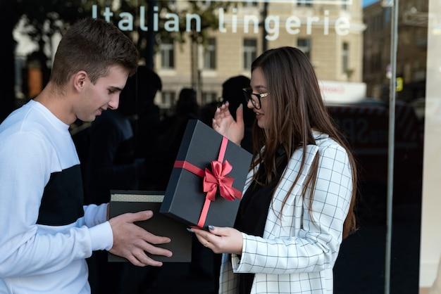 Młoda kobieta daje prezent kochankowi. dziewczyna daje prezent przyjacielowi.