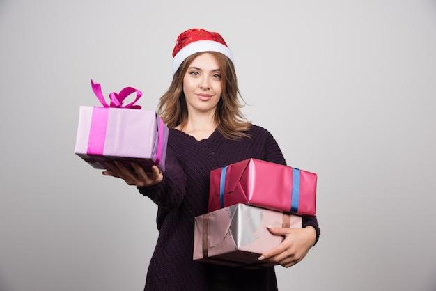 Młoda kobieta daje prezent pudełkom prezenty z santa kapeluszem.