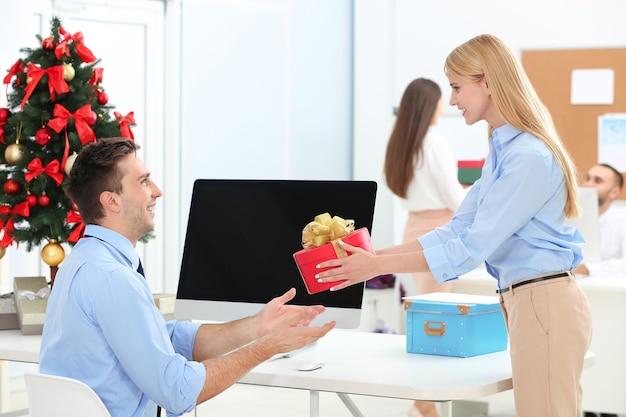 Młoda kobieta daje prezent świąteczny swojemu koledze w biurze