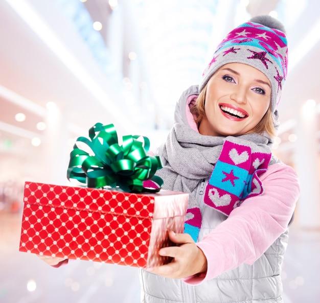 Młoda kobieta daje prezent świąteczny ubrany w zimową odzież wierzchnią