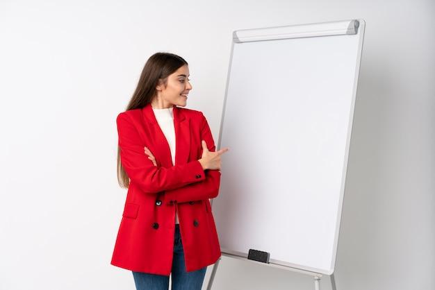 Młoda kobieta daje prezentaci na białej desce daje prezentaci na białej desce i wskazuje je