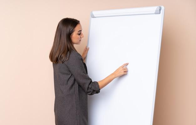Młoda kobieta daje prezentaci na białej desce daje prezentaci