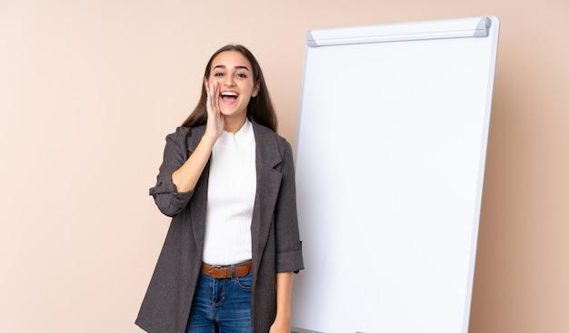 Młoda kobieta daje prezentaci na białej desce krzyczy z usta szeroko otwarty