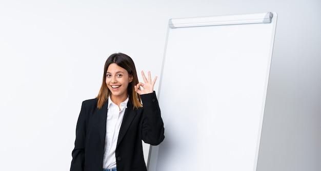 Młoda kobieta daje prezentaci na białej desce pokazuje ok znaka z palcami