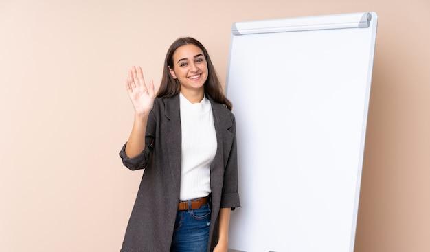 Młoda kobieta daje prezentaci na białej desce salutuje z ręką z szczęśliwym wyrażeniem