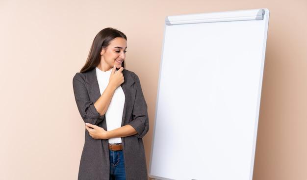 Młoda kobieta daje prezentaci na białej deski przyglądającej stronie