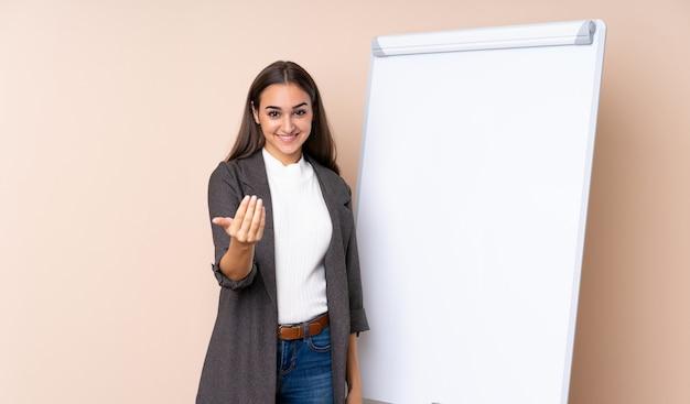 Młoda kobieta daje prezentację na białej desce zaprasza przychodzić z ręką.