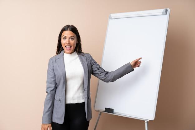 Młoda kobieta daje prezentację na białej desce zaskakującej i wskazuje palec z boku
