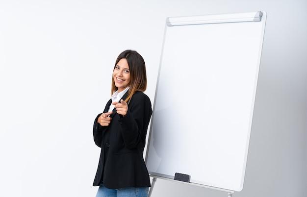 Młoda kobieta daje prezentację na białej tablicy punktach dotyka ciebie z ufnym wyrażeniem