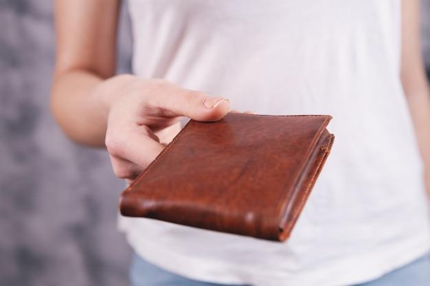 Młoda kobieta daje skórzany portfel