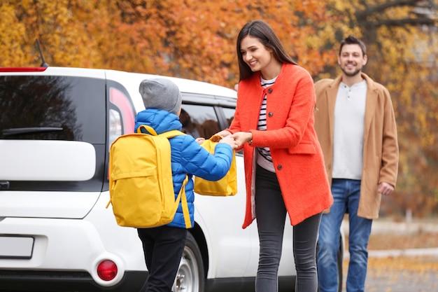 Młoda kobieta daje synowi torbę na lunch przed szkołą