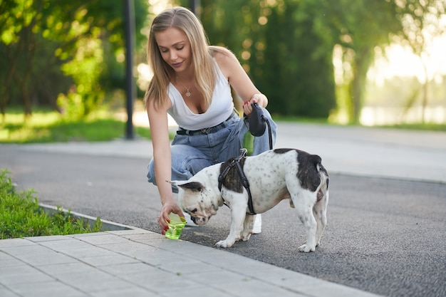 Młoda kobieta daje wodę psu w parku