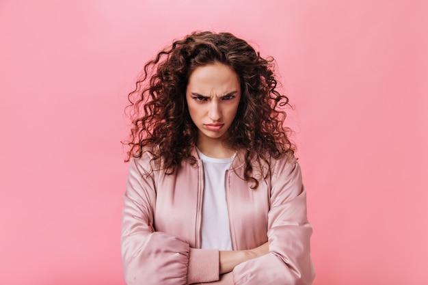 Młoda kobieta dąsa się w różowej kurtce na na białym tle