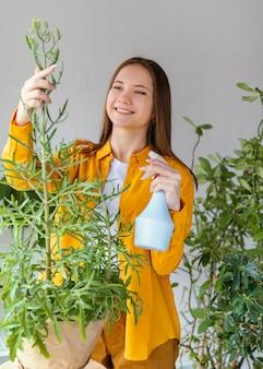 Młoda kobieta dba o swoje rośliny w domu
