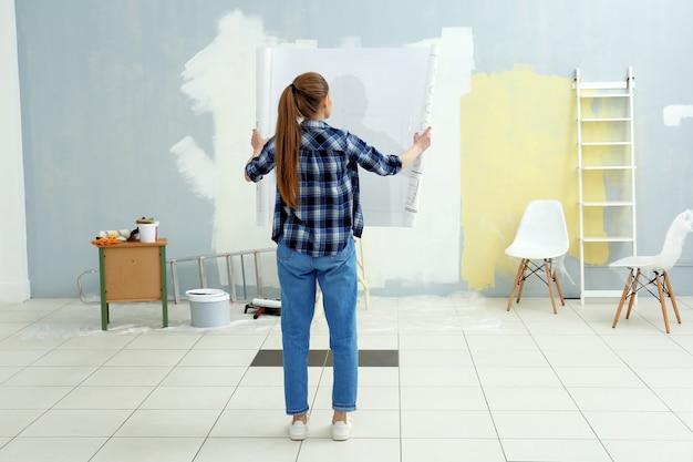Młoda kobieta dekorator z rysunkiem w pustym pokoju