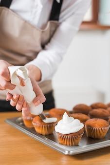 Młoda kobieta dekorowanie babeczki z białą bitą śmietaną poprzez wyciskanie w torbie cukierniczej
