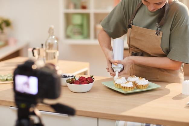 Młoda kobieta dekorowanie ciast z kremem na stole w kuchni i strzelanie do kamery