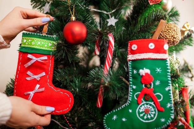 Młoda kobieta dekoruje choinkę skarpetkami w domu przygotowanie do nowego roku