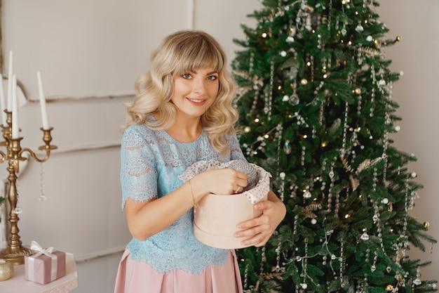 Młoda kobieta dekoruje choinkę świątecznymi zabawkami. klasyczne wnętrze w kolorze białym i złotym