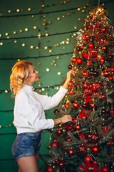Młoda kobieta dekoruje choinki
