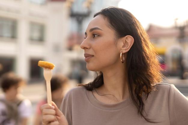 Młoda kobieta delektująca się pysznym jedzeniem ulicznym