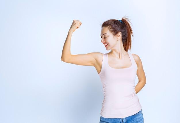 Młoda kobieta demonstruje mięśnie ramion, widok z profilu
