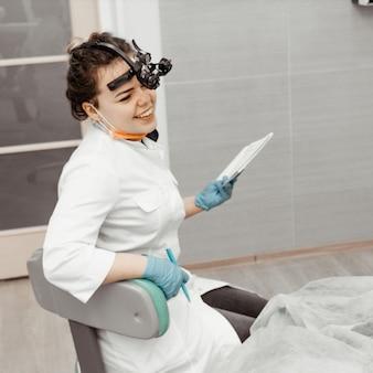 Młoda kobieta dentysta przy jej miejscem pracy. lekarz używa jednorazowych rękawiczek, maski i czapki. dentysta pracuje w jamie ustnej pacjenta, używa profesjonalnego narzędzia.