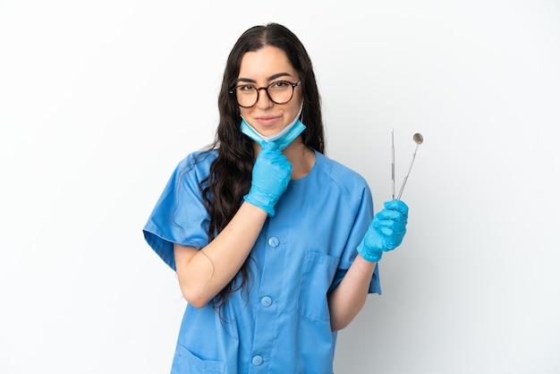 Młoda kobieta dentysta trzymając narzędzia na białym tle na białym tle myślenia