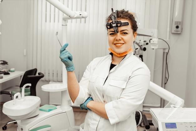 Młoda kobieta dentysty lekarka w profesjonalisty mundurze przy miejscem pracy. sprzęt do pracy w miejscu pracy dla lekarza. stomatologia