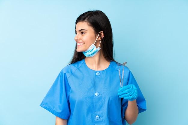 Młoda kobieta dentysty mienia narzędzia patrzeje strona