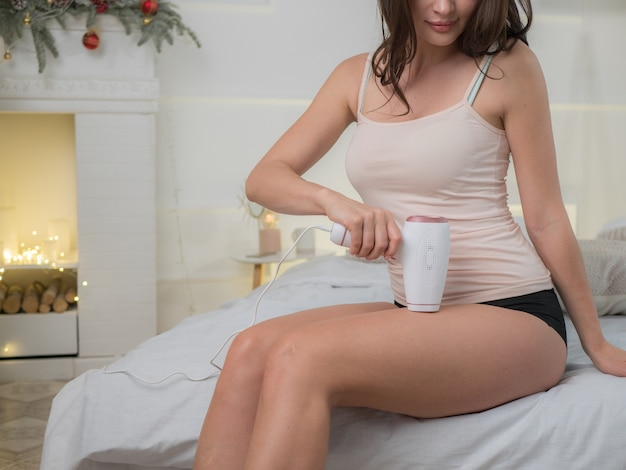 Młoda kobieta depilująca nogi w sypialni
