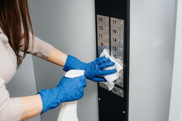 Młoda kobieta dezynfekuje i czyści klucze w windzie podczas globalnej pandemii. zostań w domu.